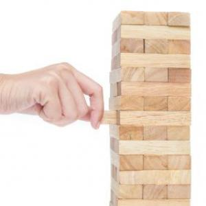 Removing a piece from a wooden stacking game.